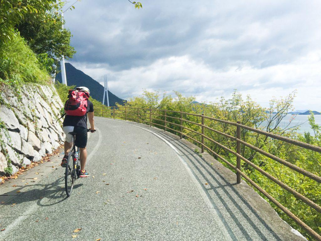 坂道をロードバイクで上る男性